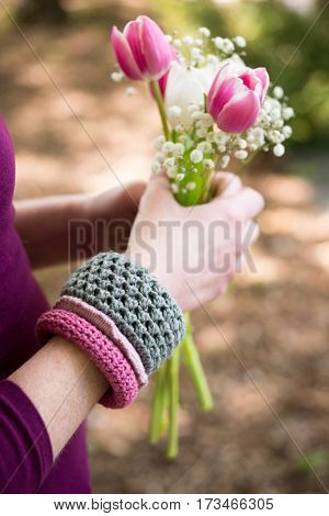 Knitted Wristbands And Hands Holding Flowers