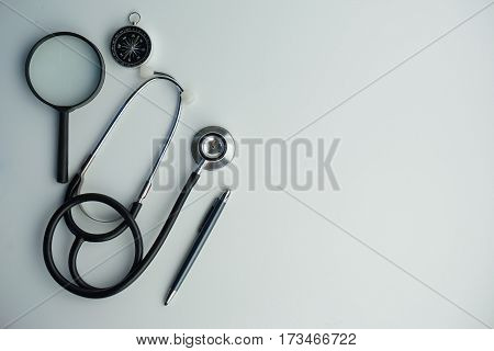 Top view of stethoscope, compass, magnifying glass, pen and eye glasses on white background. Flat lay and copy space. Medical Concept.