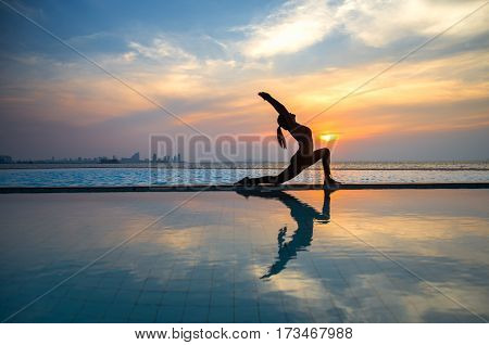 Silhouette young woman practicing yoga on swimming pool and the beach at sunset.