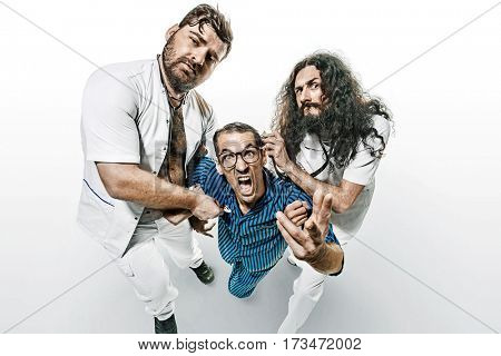 Two funny doctors holding a psycho patient