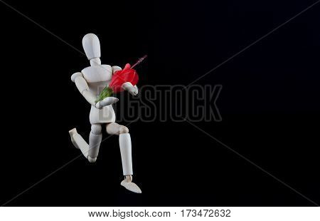 Wooden Figurine Kneeling With Flower On Black Background With Copy Space. Wedding, Engagement, Valen