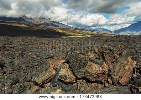 Lava field at the Tolbachik volcano, after eruption in 2012 on background Big Udina volcano and Plosky Tolbachik volcano, Klyuchevskaya Group of Volcanoes