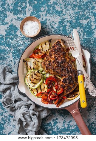 BBQ chicken and grilled vegetables in a cast iron skillet on a dark background top view. Delicious healthy food