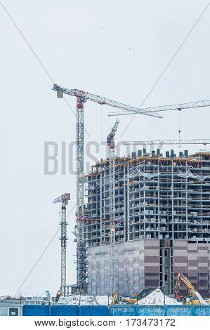modern urban hiht building under construction with a crane. Construction of the new building. Construction cranes