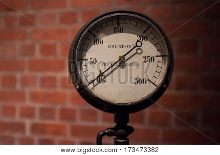 Vintage pressure gauge on blurred brick wall background with arrow pointing at zero