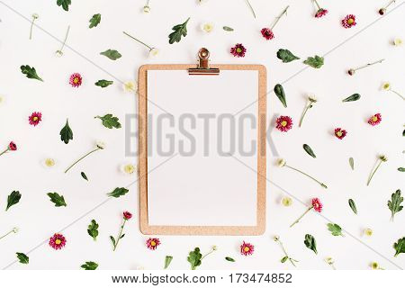 Clipboard mock up and wildflower pattern. Flat lay top view. Flower background.