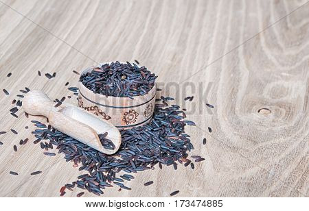 black rice in a wooden bowl on table