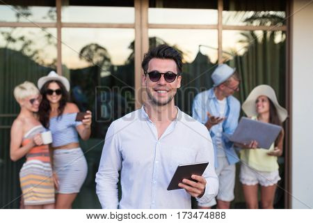 Young People Group On Terrace Tropical Hotel, Friends Using Cell Smart Phone Tropic Holiday Vacation Green Forest