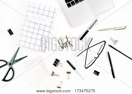 White office desk frame with word Work and supplies. Laptop notebook scissors pen clips glasses and office supplies on white background. Flat lay top view mockup.