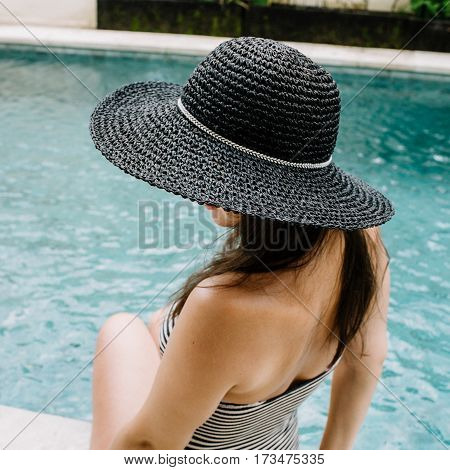Young woman in hat relaxing near swimming pool.