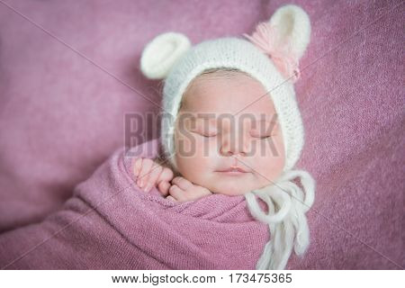 A newborn baby sleeps in a hat with ears on a pink blanket