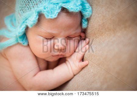 Newborn baby sleeping on a blanket. Hands under cheek