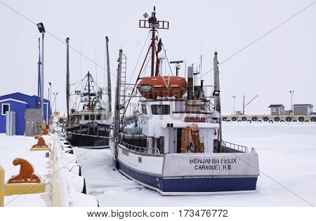 Caraquet, New Brunswick, February 5, 2017 -- Close up of colorful fishing boats at the snow covered docks in the frozen waters of Chaleur Bay at Caraquet, New Brunswick on a chilly overcast day in February.