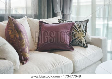 Beautiful Purple And Green Pillows On White Sofa In Living Room