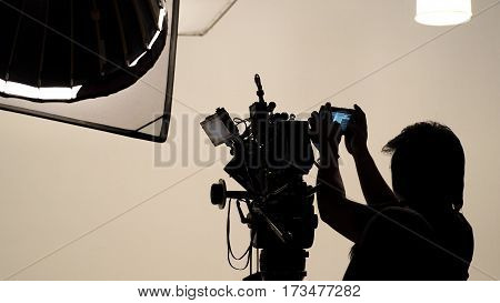 Silhouette Of Photographer Checking For Movie Camera.