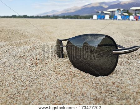 Sun protection glasses in the sand closeup