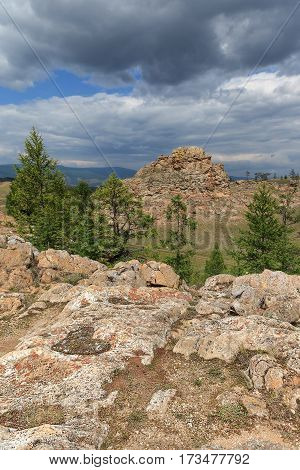 Mountain landscape with textured rocks coniferous trees and heart form in the foreground. View from above