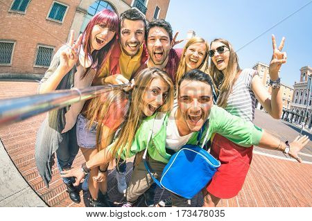 Group of multicultural tourists friends having fun taking selfie and shouting out at old town tour -Travel lifestyle concept with happy people wandering around city landmarks - Vivid saturated filter