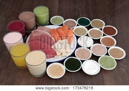 Health food and drinks for body builders with lean meat of steak, chicken and pork with salmon and dietary supplement powders on oak background.