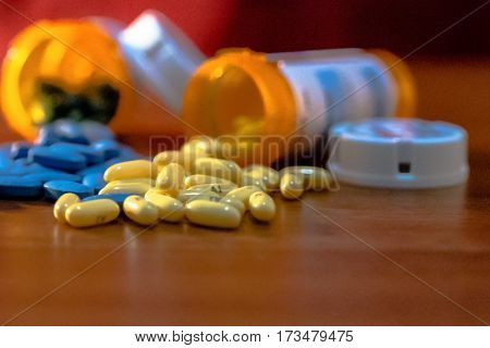 yellow and blue pills on a table with overturned prescription bottles out of focus and a red background