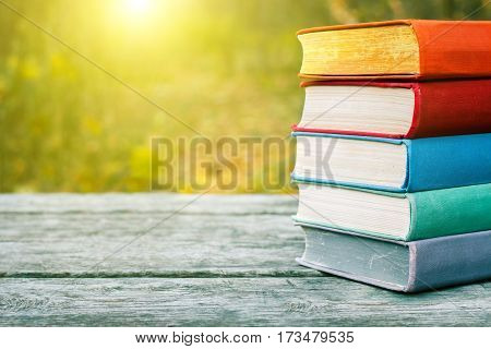Books on the old wooden table at the nature background. Concept: back to school education.
