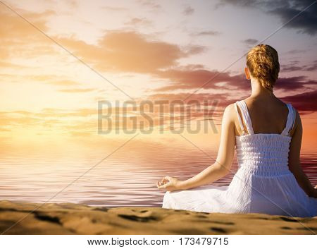 Young woman doing yoga in sunset