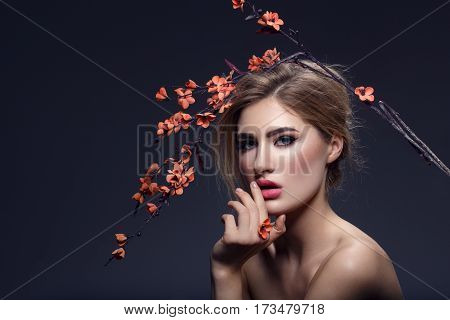 Beautiful young woman with make-up and loose hairdo holding artificial sakura branch with orange flowers. Beauty shot on dark background. Copy space. poster