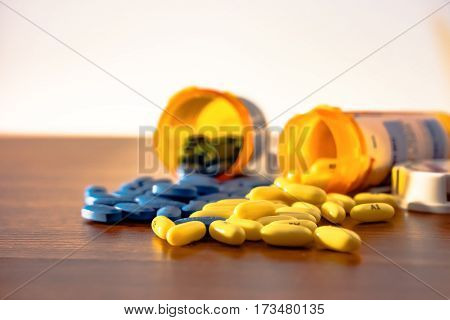 Two prescription bottles overturned with blue and yellow pills spilling onto the wooden table with whit background.