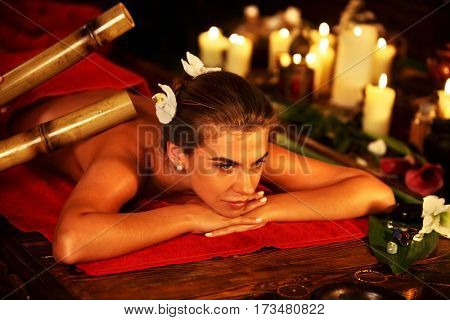 Bamboo decor of woman massage in spa salon. Girl on candles background in massage spa salon. Luxary interior in oriental therapy salon. Female have relax big stick after sport on red towel. Close up