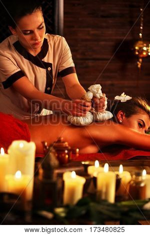 Aromatherapy massage of woman in spa salon. Girl ayurvedic herbs massaging spa salon. Luxary interior in oriental therapy salon. Close up of female massage hands give herbs hot ball therapy. Burning