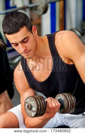 Men in gym workout weights with fitness equipment. Man holding dumbbell workout at gym. Chrome dumbbells in strong male hands.