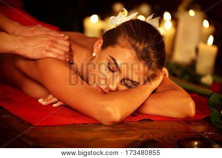 Massage therapy deals. Woman in spa salon. Girl on candles background treats problem back spa salon. Luxary interior with working masseuse in therapy salon. Female bare back with smooth skin relax .