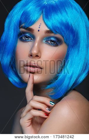 Beautiful young woman with glowing skin, fashion make-up and metallic nails in short blue hair wig. Beauty shot on black background. Copy space.