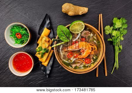 Asian soup pho bo with spring rolls, top view, served on black stone.