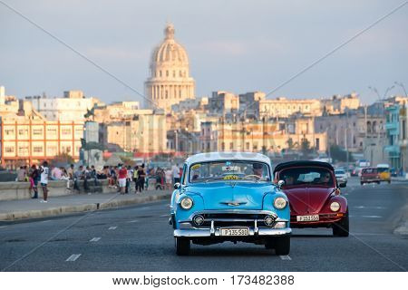 HAVANA,CUBA - FEBRUARY 24,2017 : A classic american car travels along the Malecon seaside avenue in Havana with the iconic Capitol building on the background