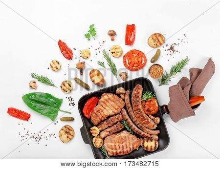 Cast iron grill pan with steak and sausages grilled on a white background with grilled vegetables. Top view. Flat lay
