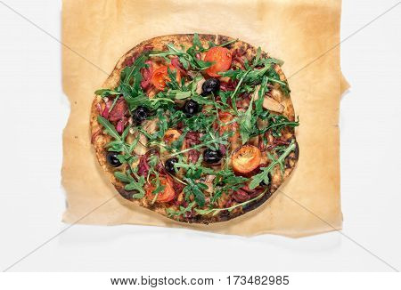 Vegetarian pizza with marinated red onions mushrooms tomatoes olives and arugula on white background top view. Delicious and healthy food