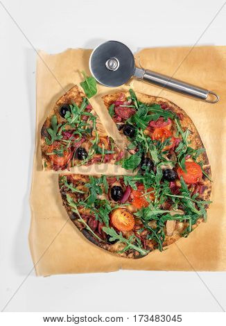 Vegetarian pizza with marinated red onions mushrooms tomatoes olives and arugula on white background close up top view. Delicious and healthy food