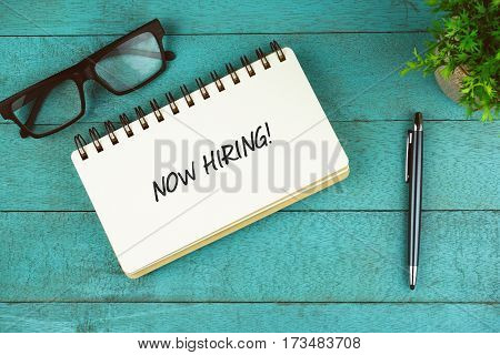 Business Concept. Top view of eye glasses, plant, pen and open notebook written with Now Hiring! on blue wooden background.