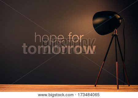 Hope for tomorrow motivational quote on office wall illuminated with desk lamp