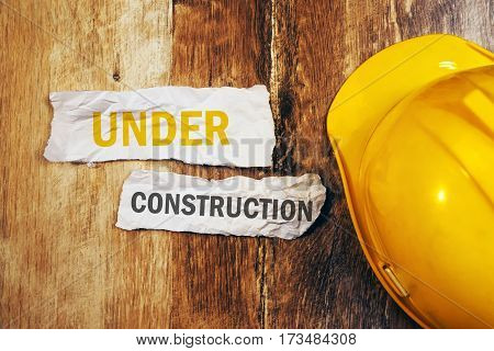 Under construction concept with protective yellow hard hat helmet on wooden desk