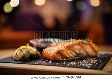 Grilled Scottish salmon with soy sauce and herb by lemon served on a stone board