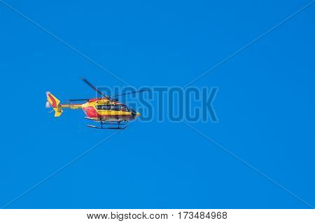 Red and yellow rescue helicopter moving in blue sky with blur propeller