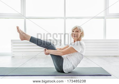 Cheerful senior woman is doing exercise in morning. She is sitting and stretching legs up with happy smile