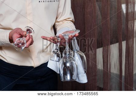 Waiter in italian restoraunt with four wineglass