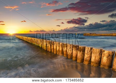 Baltic sea at beautiful sunrise,wooden breakwater in the light of the setting sun,Baltic sea,Poland