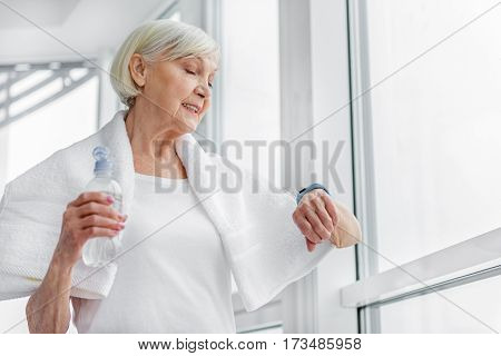 Joyful old woman is using tracker after workout. She is standing near window and smiling. Woman is holding bottle of water