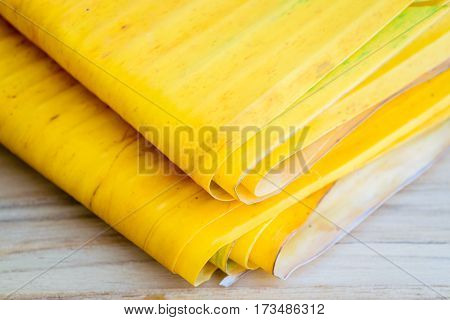 Yellow banana leaf  bundle together on wooden table