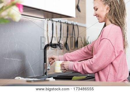 Woman Pouring Water In Her Kitchen