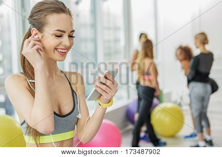Cheerful young female person is standing in gym separately from group. She holding earphones and smartphone